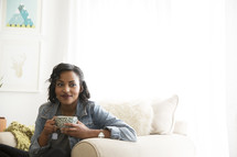 An African American woman holding a cup of hot tea