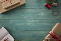 border of wrapped gifts on a wood floor with a Christmas gift list.