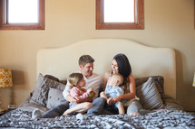 a family sitting together on a bed
