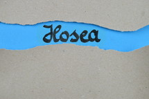 Hosea - torn open kraft paper over blue paper with the name of the prophetic book Hosea