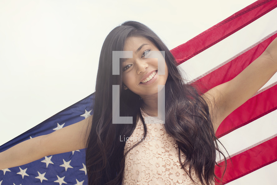 A young woman holding an American flag