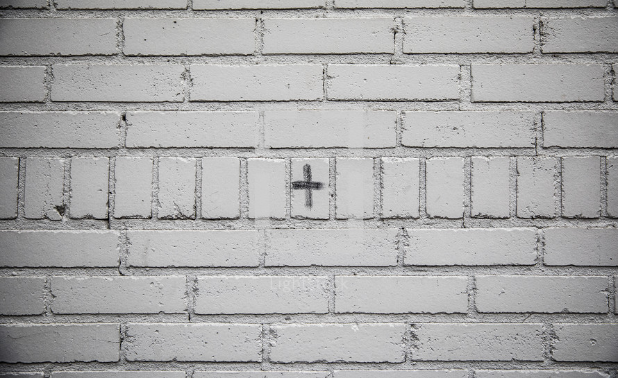 cross in ashes on a white brick wall