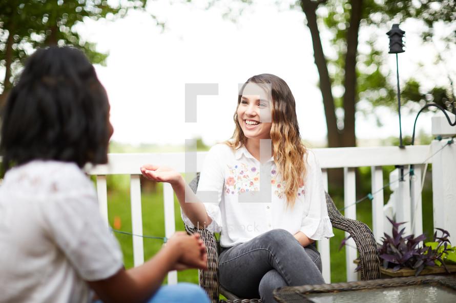 women talking on a patio