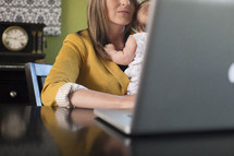 working mom, mother holding her infant daughter while typing on a laptop