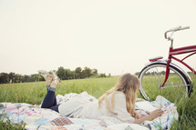 young woman reading on a blanket in the grass, next to her bicycle