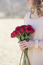 woman holding a bouquet of red roses outdoors