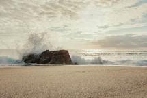 waves crashing into a rock on a beach