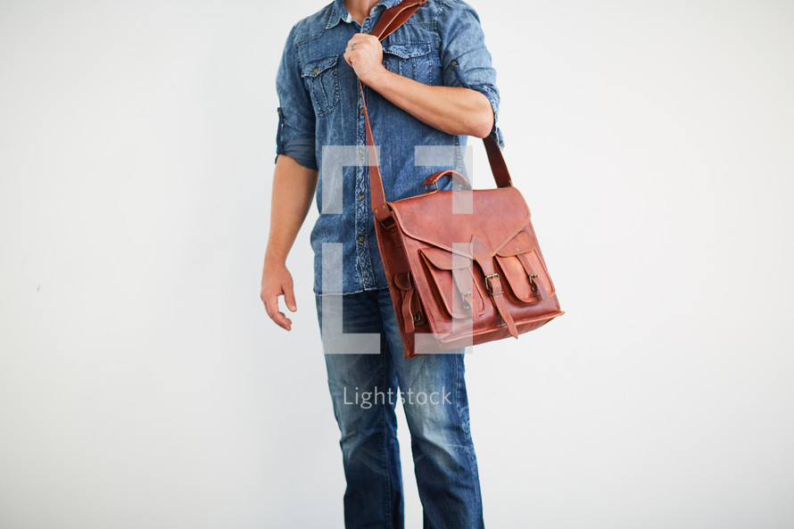 a man standing holding a messenger bag