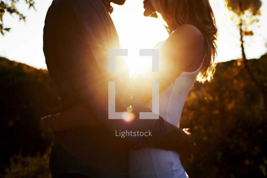 the glow of sunlight on a couple hugging