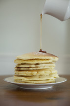 pouring syrup on a stack of pancakes