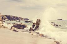 waves crashing into rocks on a beach