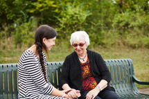 Mature woman laughing and talking with a young woman on a park bench