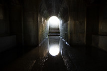 reflection in water at the bottom of a dark tunnel.