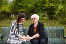 elderly woman praying with a young woman on a park bench