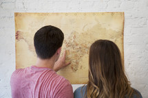 a couple looking at a world map together