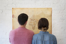a couple looking at a world map