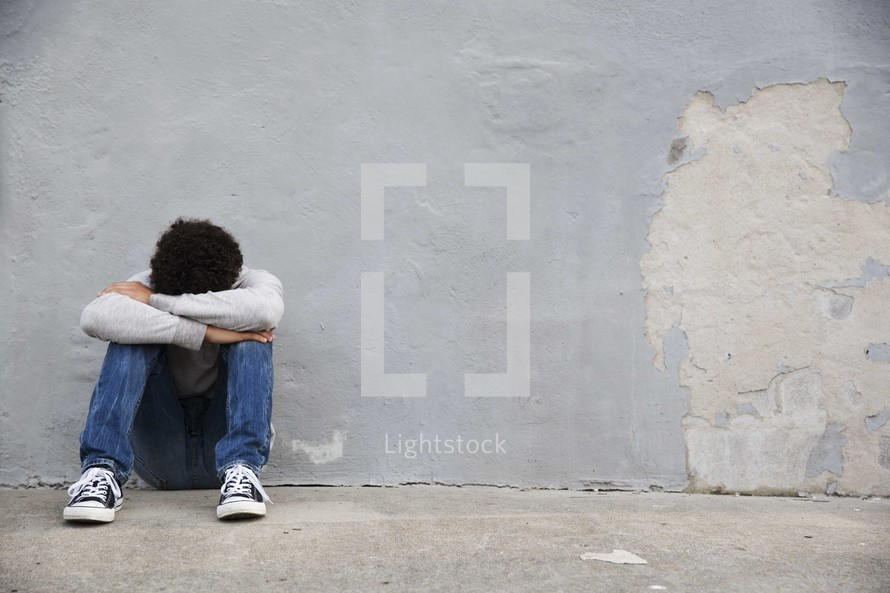 a depressed teen boy sitting alone.