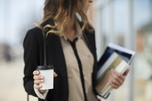 a career woman carrying a stack of books and a coffee cup