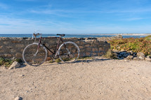 bike leaning against a stone wall on a beach
