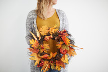 a woman standing holding a fall wreath