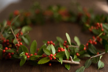 a holly wreath on a wood table