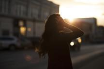 a woman walking down a sidewalk at sunset tucking her hair behind her ear