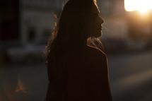 a woman walking down a sidewalk at sunset looking back at the camera
