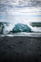 Sea waves crashing into ice and rocks on a shore in Iceland