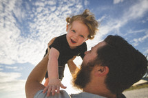 man holding his toddler son in the air