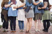 A group of young women with their arms around each other and holding Bibles.