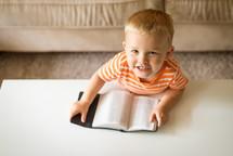 a toddler boy reading a Bible