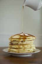 pouring sugar on a stack of pancakes