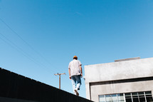 a man walking across the ledge of a building