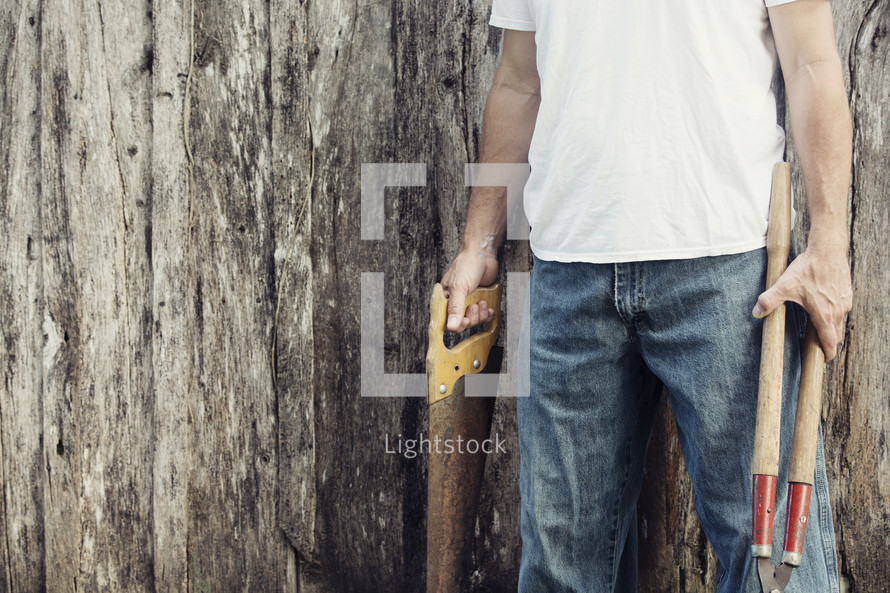 man holding saw and clippers
