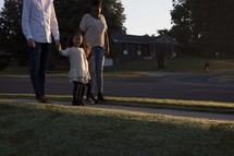 a family walking together down a sidewalk holding hands