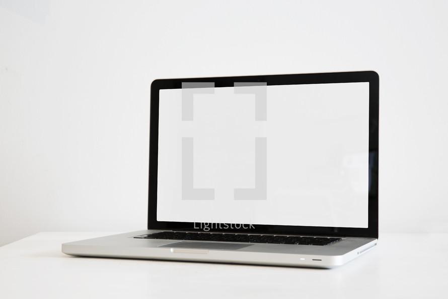 blank laptop computer screen on a white desk.