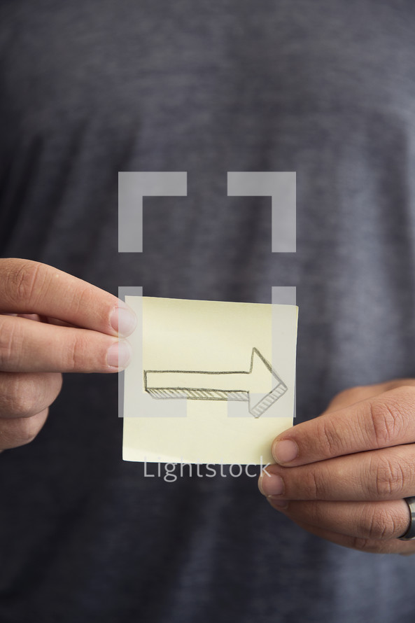 man holding a post-it note with an arrow
