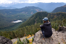 a woman sitting at the top of a mountain