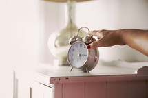 woman's hand reaching for an alarm clock in her room.