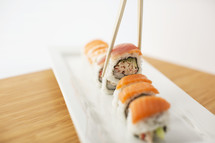 Chopsticks picking up a piece of sushi from a sushi roll.