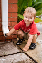 toddler boy playing with a rain spout