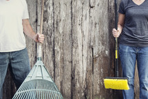man and woman holding yard tools