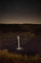 stars in the night sky above a waterfall