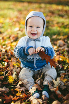 toddler boy playing in fall leaves