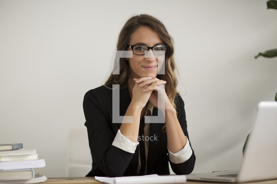 a happy businesswoman sitting at her desk.