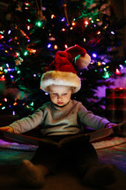a child reading a book under a Christmas tree