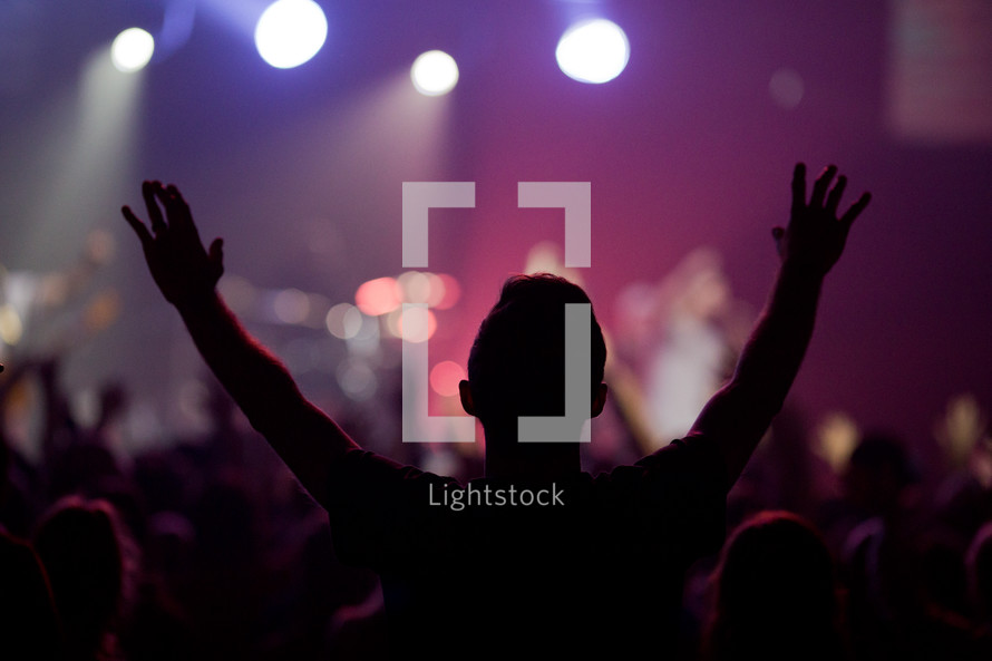 silhouettes of people in an audience at a concert with raised hands
