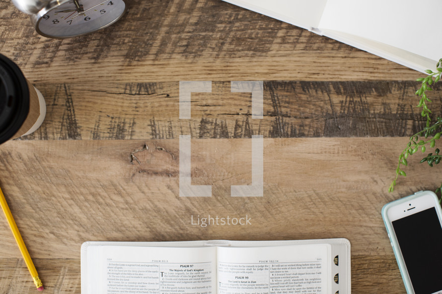 coffee cup, pencil, open Bible, journal, and cellphone on a desk
