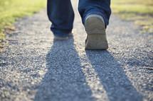 man walking away on a gravel road.