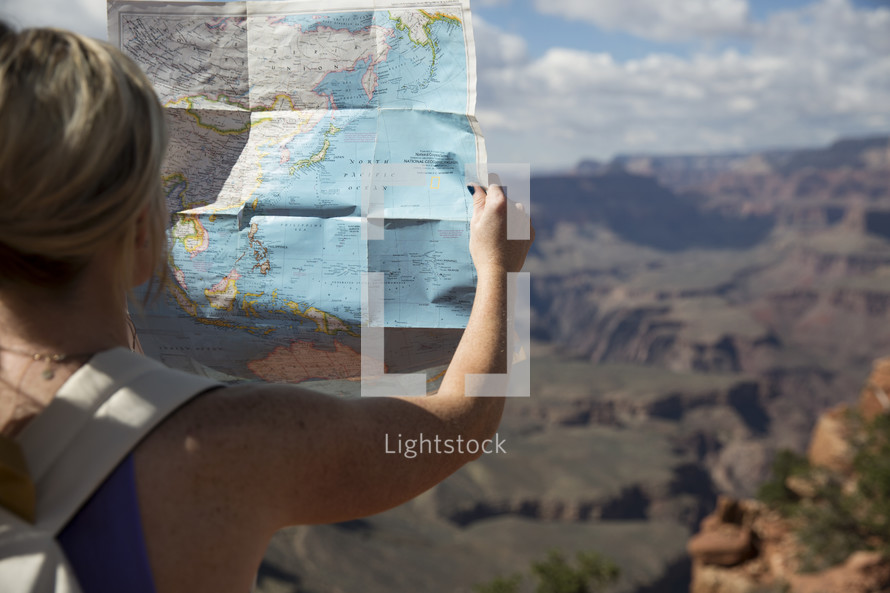 woman standing at the edge of a canyon cliff reading a map